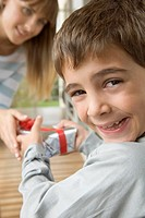 Young boy smiling and taking gift from mother (thumbnail)