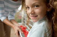 Young girl smiling and taking gift from mother (thumbnail)