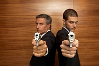 Portrait of two businessmen standing back to back and holding handguns (thumbnail)