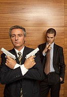 Portrait of a businessman holding handguns with another businessman smoking a cigar behind him