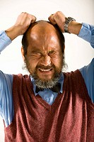 Close-up of a mature man pulling his hair