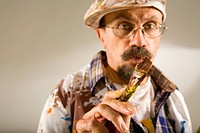 Portrait of a mature man holding a paintbrush