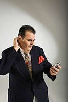 Businessman holding a mobile phone and looking confused