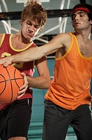 Low angle view of two young men playing basketball (thumbnail)