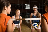 Four young women playing volleyball