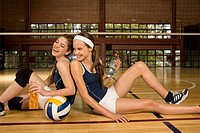 Side profile of two young women sitting in a volleyball court and smiling