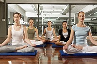 Five young women meditating in a gym