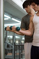 Two young men exercising with dumbbells in a gym