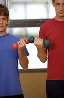 Portrait of two young men exercising with dumbbells
