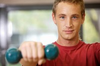 Portrait of a young man exercising with a dumbbell (thumbnail)