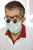 Portrait of a male dentist looking through magnifying glass