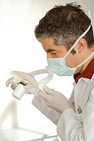 Close-up of a male dentist adjusting a medical equipment