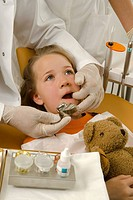 Dentist examining a girl's teeth