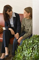 Young woman talking to a boy in a waiting room (thumbnail)