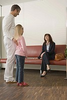 Male doctor standing with a girl and talking to a young woman