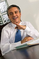 Businessman sitting at a desk and smiling (thumbnail)
