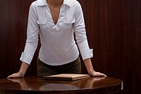 Mid section view of a businesswoman leaning over a desk