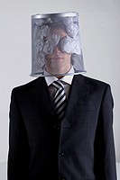 Businessman hiding his face with a wastepaper basket