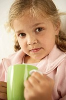 Portrait of a girl holding a cup and looking serious (thumbnail)
