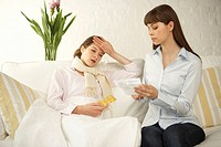 Mid adult woman suffering from fever with her friend reading a medicine bill beside her