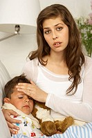 Portrait of a mid adult woman sitting with her son suffering from fever