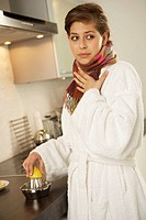 Side profile of a mid adult woman squeezing a lemon in the kitchen