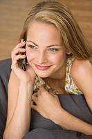 Close-up of a young woman using a mobile phone and smiling (thumbnail)