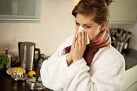 Close-up of a mid adult woman sneezing in the kitchen