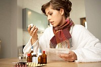 Close-up of a mid adult woman checking medicines with their bill