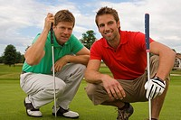 Two mid adult men crouching on a golf course and smiling (thumbnail)