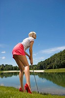 Side profile of a mid adult woman playing golf on a golf course (thumbnail)