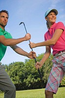 Side profile of a mid adult couple holding a golf club