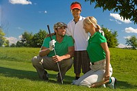 Portrait of a boy standing with his arm around his parents in a golf course
