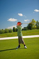 Side profile of a boy swinging a golf club