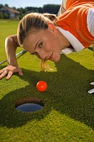 Portrait of a mid adult woman judging a golf ball on a golf course