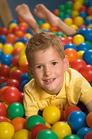 Portrait of a boy lying in a ball pool and smiling (thumbnail)