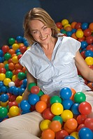 Portrait of a mid adult woman sitting in a ball pool and smiling