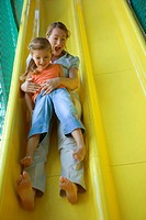 Mid adult woman with a girl sliding on a slide