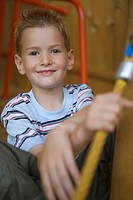 Portrait of a boy sitting on a slide and smiling