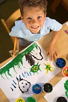 High angle view of a boy painting and smiling
