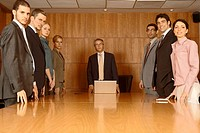 Group of business executives standing in a board room