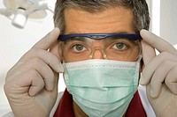 Portrait of a male dentist adjusting his protective eyewear