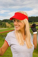 Mid adult woman holding a golf club and smiling