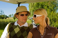 Close-up of a mid adult couple sitting in a golf cart