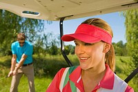 Close-up of a mid adult woman smiling in a golf cart with a mid adult man playing golf in the background