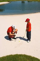 High angle view of a mid adult man giving golf training to his son