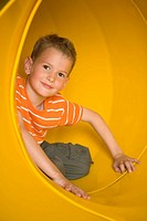 Portrait of a boy sitting in a tubular slide and grinning