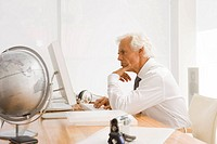 Side profile of a businessman working on a desktop PC in an office