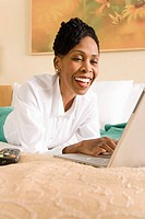 Businesswoman lying down on bed using laptop