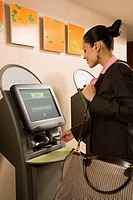 Businesswoman using self check-in computer terminal